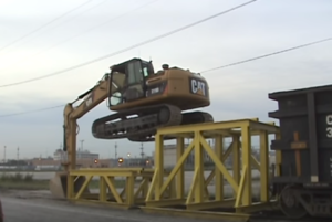 Caterpillar Climbs  Railcar To Unload Rock!
